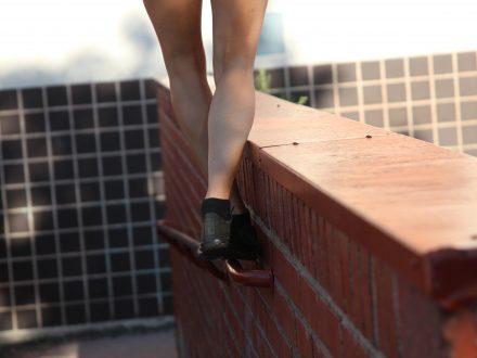 Henkilö kävelemässä kaiteen reunalla. Kuvassa näkyy jalat sekä kengät.