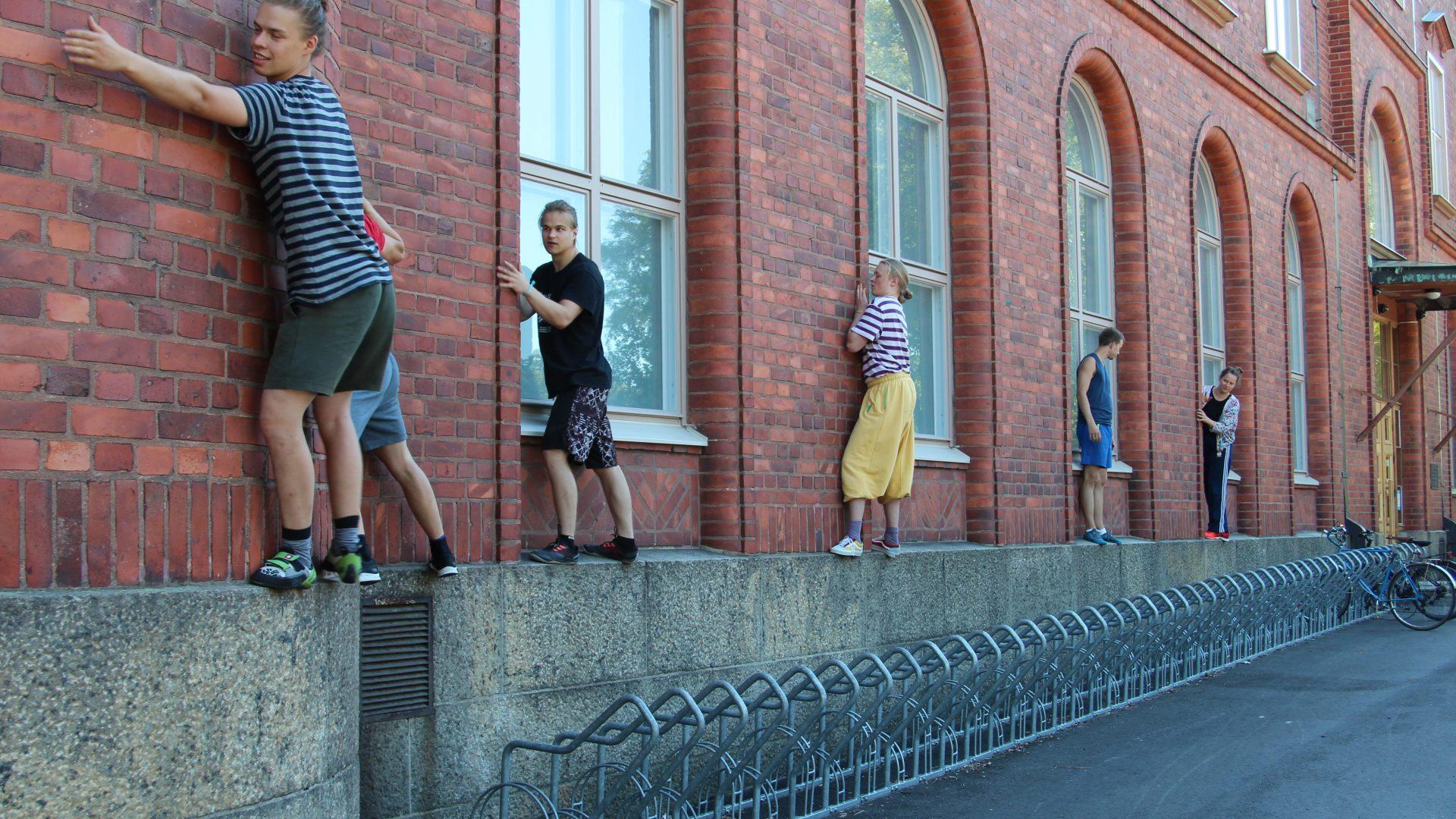 Ihmisiä kiipeilemässä talon seinällä. Auringonvalo. Pyöräteline. Tiilitalo. Isot ikkunat.